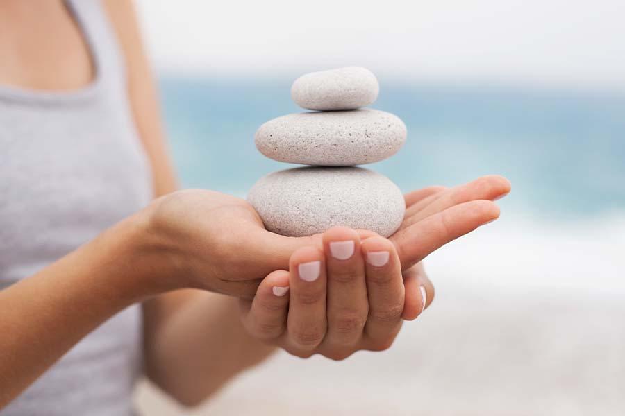 stones balanced on hand with sea behind